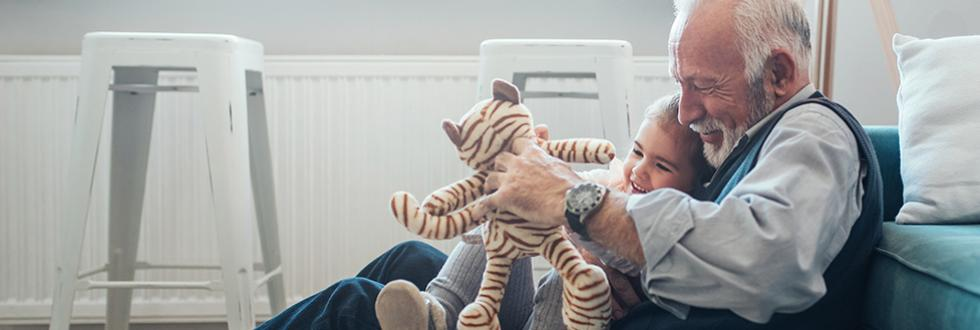 Grandfather and grandchild playing with a stuffed animal